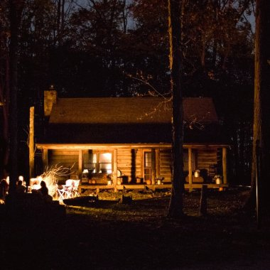 log cabin in the woods, people gathered around a fire