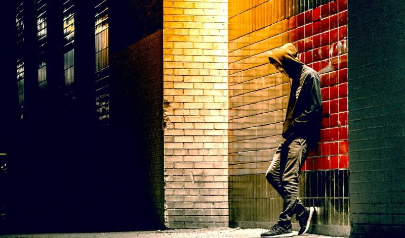man leaning against wall in alleyway, lonely