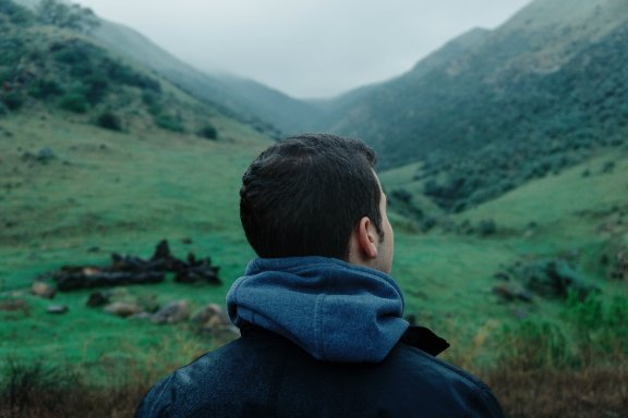 Man facing a mountain, looking at the right side.