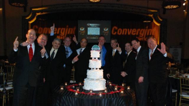 Celebrating group photo around a cake header image