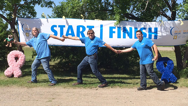 Convergint day Regina male colleagues holding hands during group photo