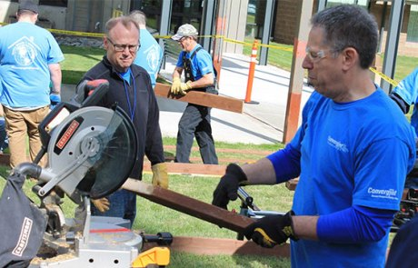 Colleagues working with saw on Convergint day
