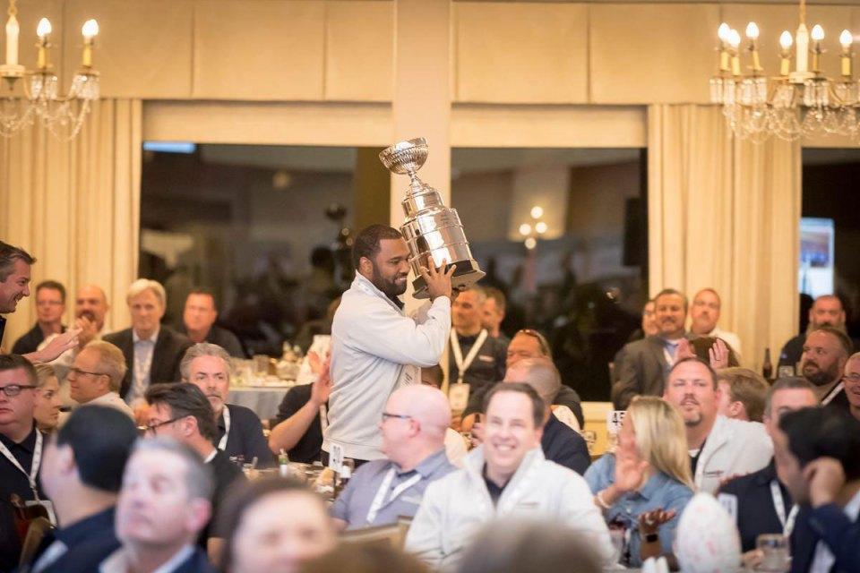 Convergint Colleague lifting an award in the air