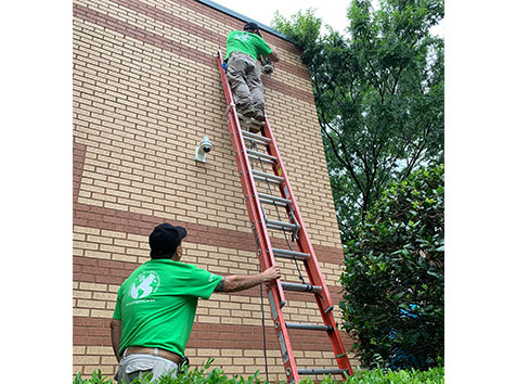 Men installing security camera, one on ladder and the other holding