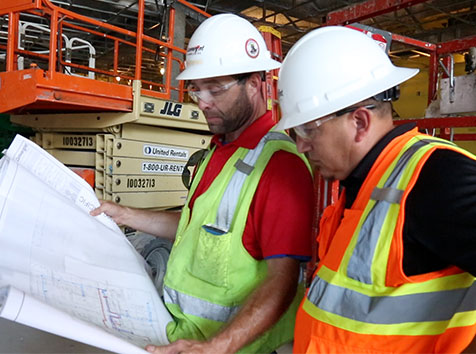two men looking at blueprints
