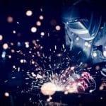 Man welding a piece of steel while wearing welding helmet