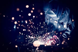 Man welding a piece of steel while wearing welding helmet