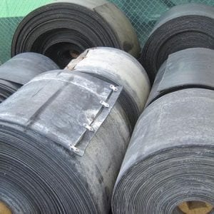 Fenced area of warehouse with giant rolls of used conveyor belts