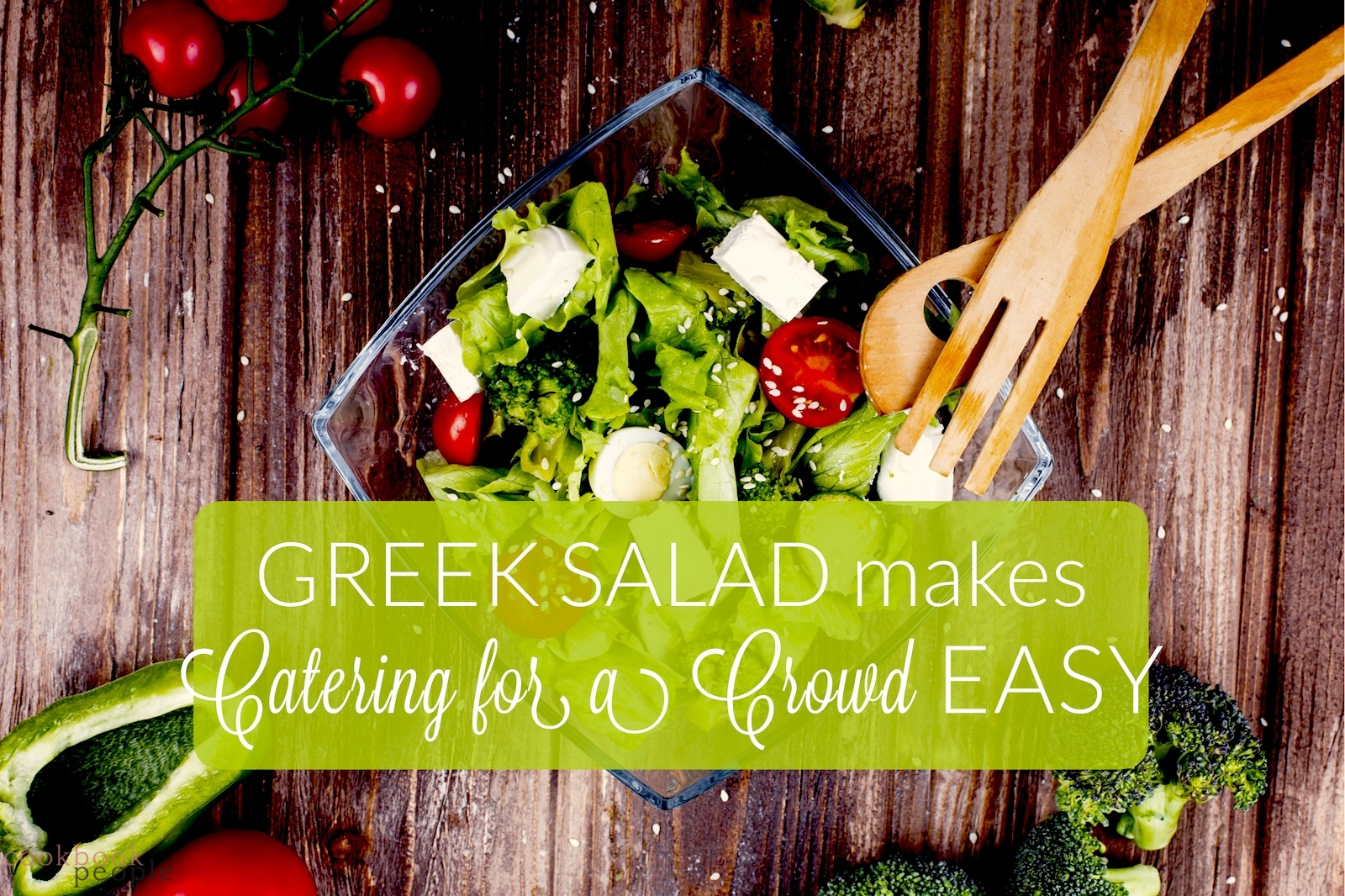 Greek salad on wooden table with title: Greek Salad Makes Catering for a Crowd Easy