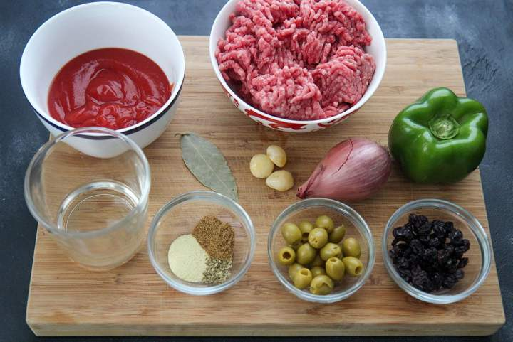 twelve ingredients in small bowls on a wooden board
