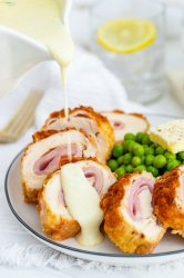 chicken cordon bleu on a plate with sauce on top and green peas on the side.