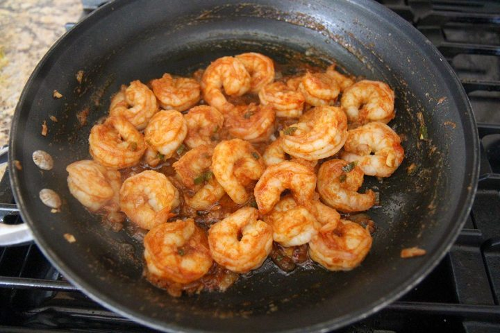 shrimp cooking in a black skillet on a stove top.
