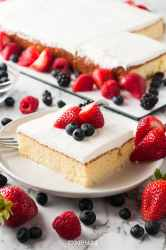 a slice of tres leches cake on a white plate with berries