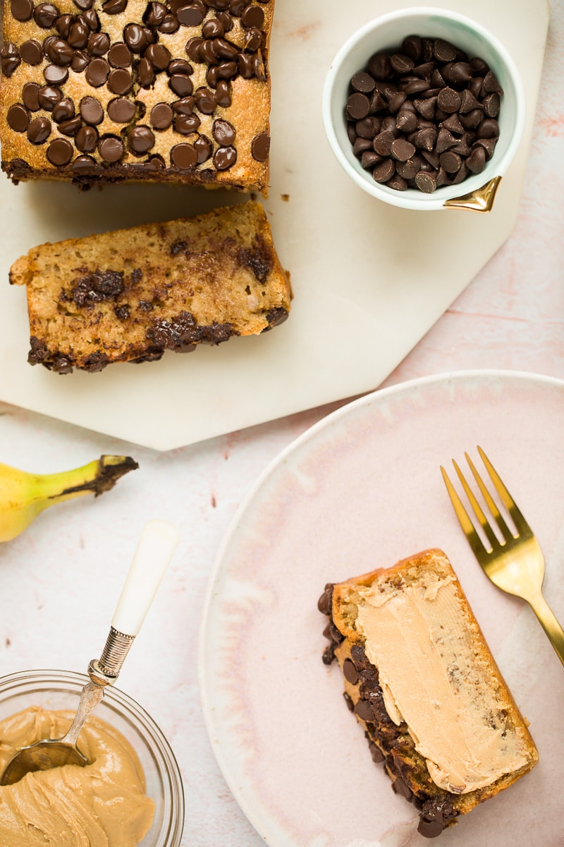 banana bread, chocolate chips in a small bowl, a banana, peanut butter in a bowl, and a slice of banana bread with smeared peanut butter and a fork on the side.
