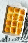 a dozen baked dinner rolls in a white baking dish on top of a white and blue kitchen towel.