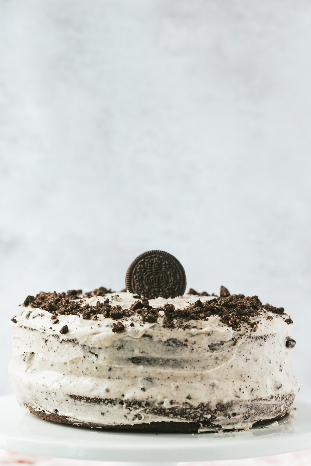 a two layer oreo cake with one oreo cookie on top and crumbs around the sides. A light background.