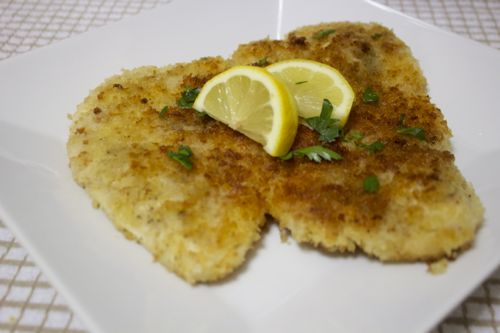 Breaded and fried chicken schnitzel recipe served with lemon wedges