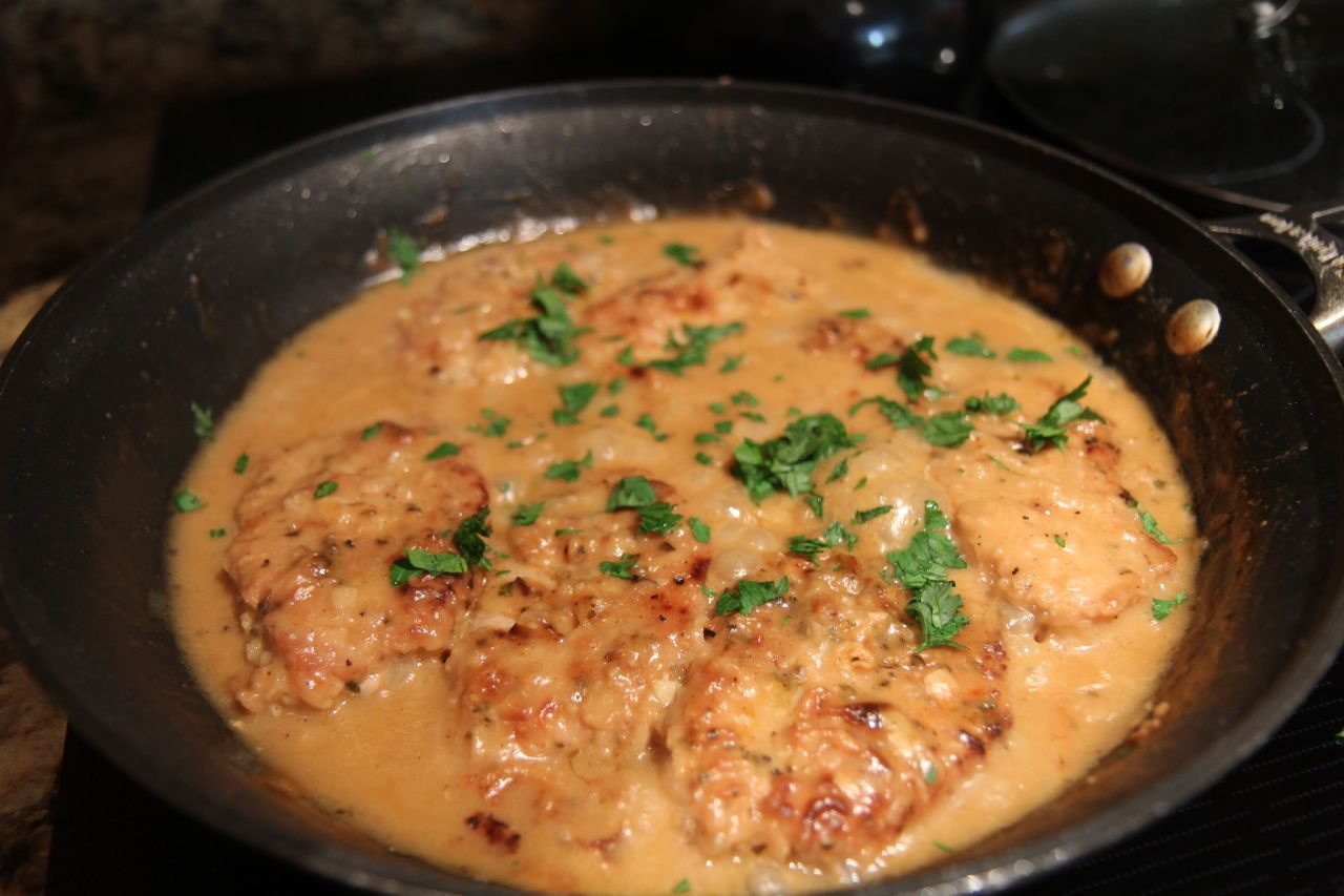 smothered pork chops, parsley, in a black skillet.
