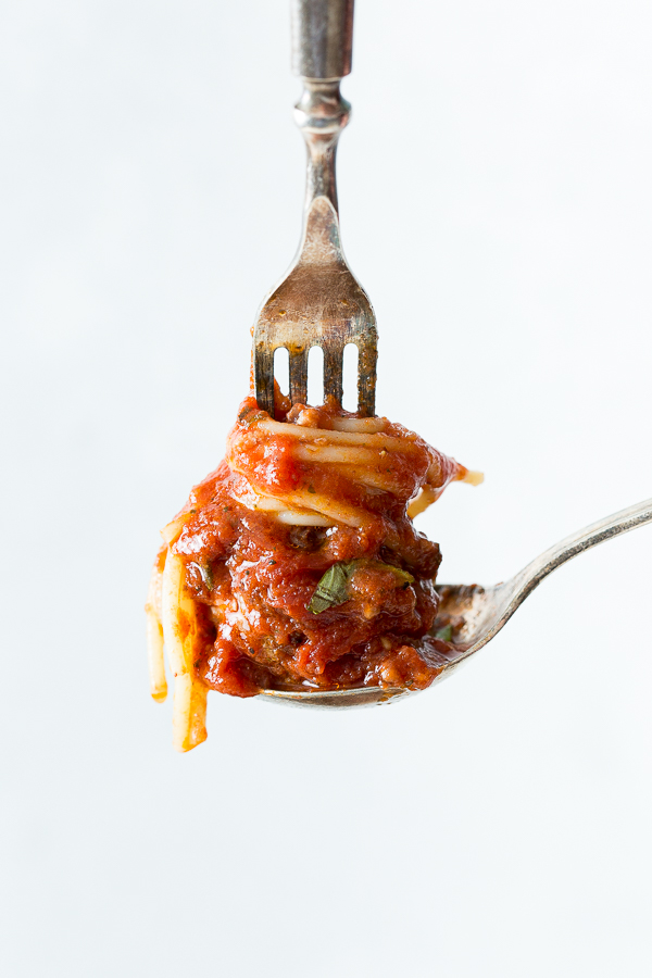 a spoon holding a small portion of spaghetti and a meatball with a fork on top.