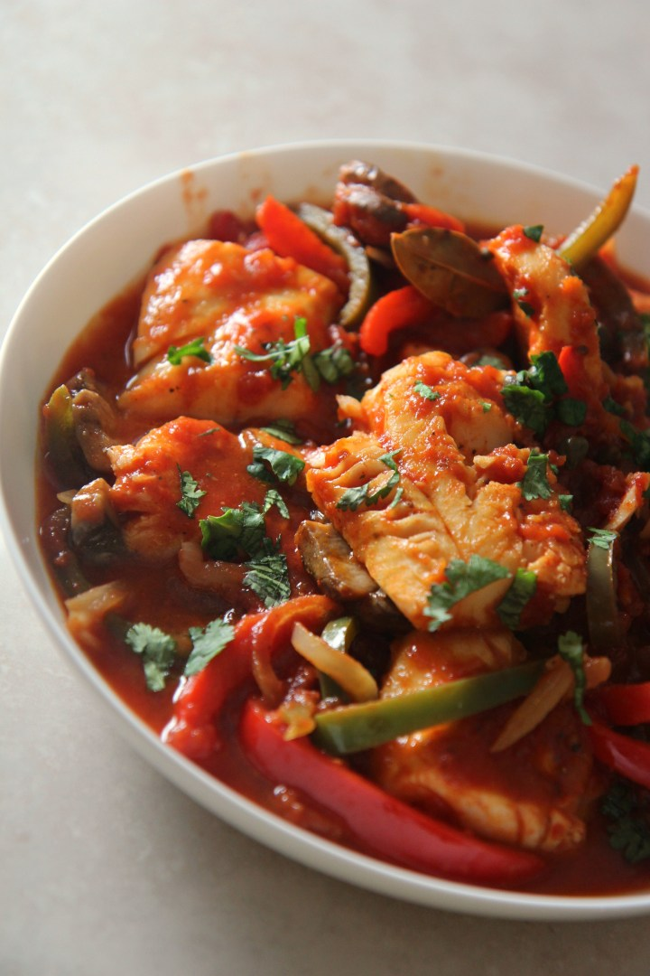 Delicious skillet cod dinner served in a bowl with tender red and green peppers, onions, and a herb garnish.