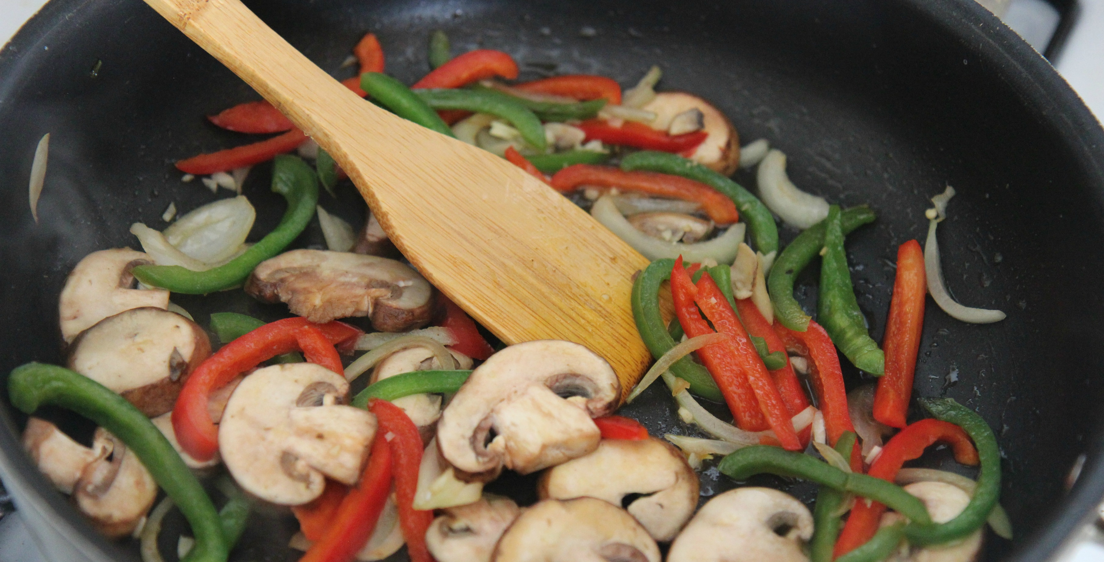 Saute the vegetables together in a skillet with some oil. Vegetables include mushrooms, onions, and red and green peppers.