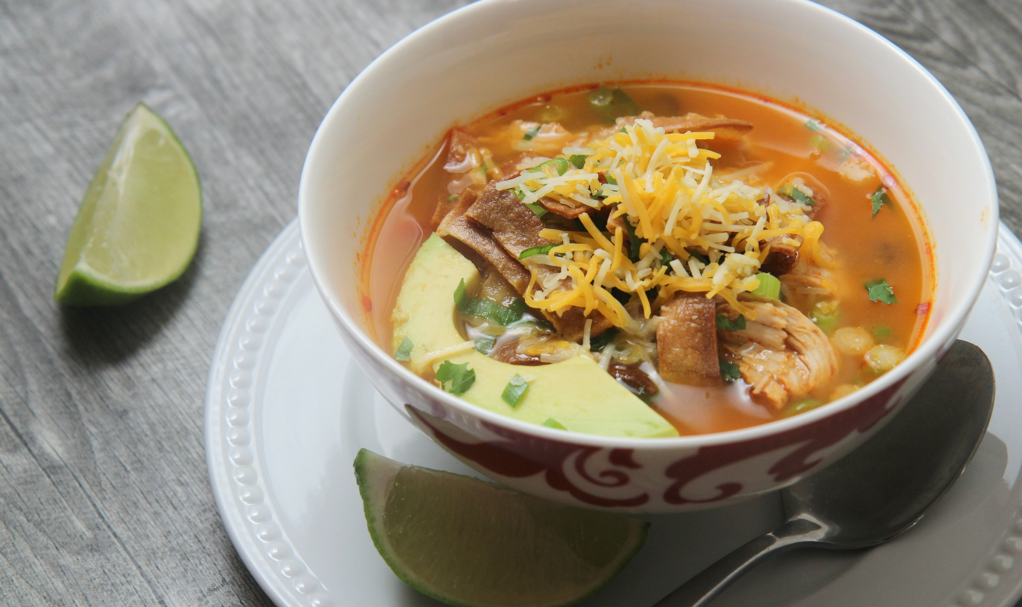 A warm bowl of this spicy chicken tortilla soup topped with cheddar cheese and avocado is a perfect cold-day remedy