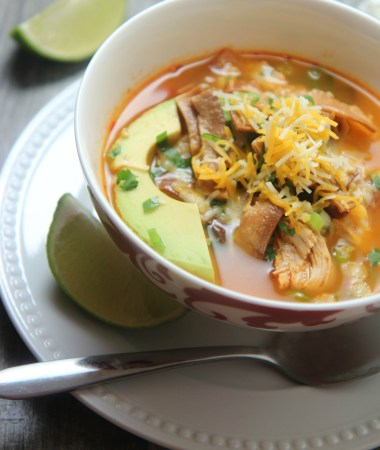 spicy chicken tortilla soup in a white bowl with a spoon