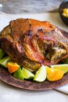 roasted pork on a brown plate with limes and oranges