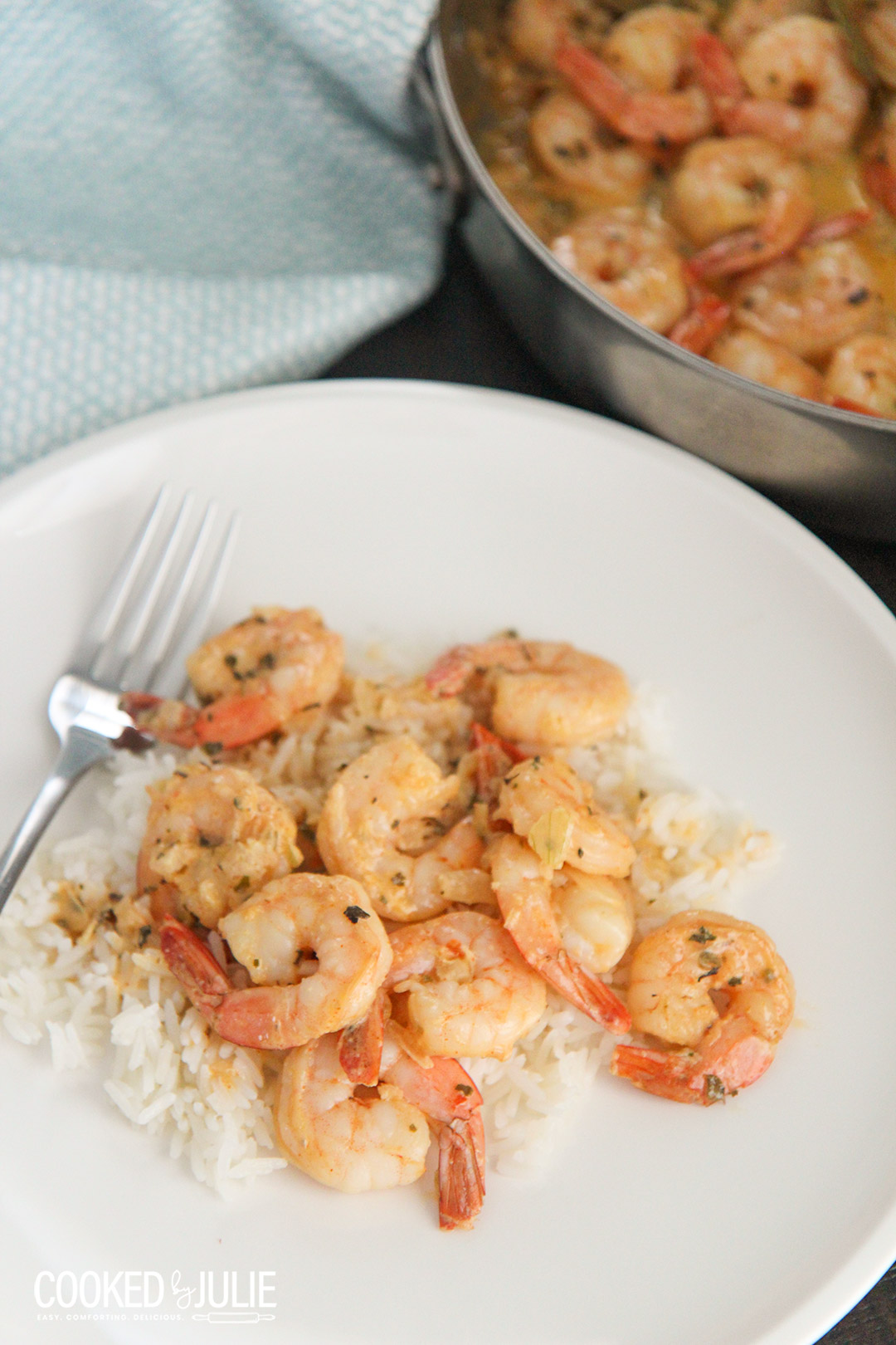 shrimp over white rice on a white plate with a fork