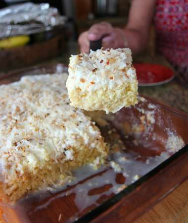 a hand lifting a slice of coconut tres leches and a full cake in the background.