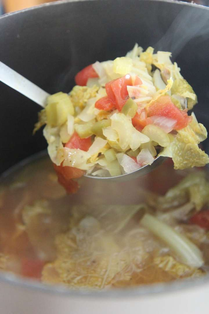 a ladle filled with cabbage soup over a pot filled with soup.