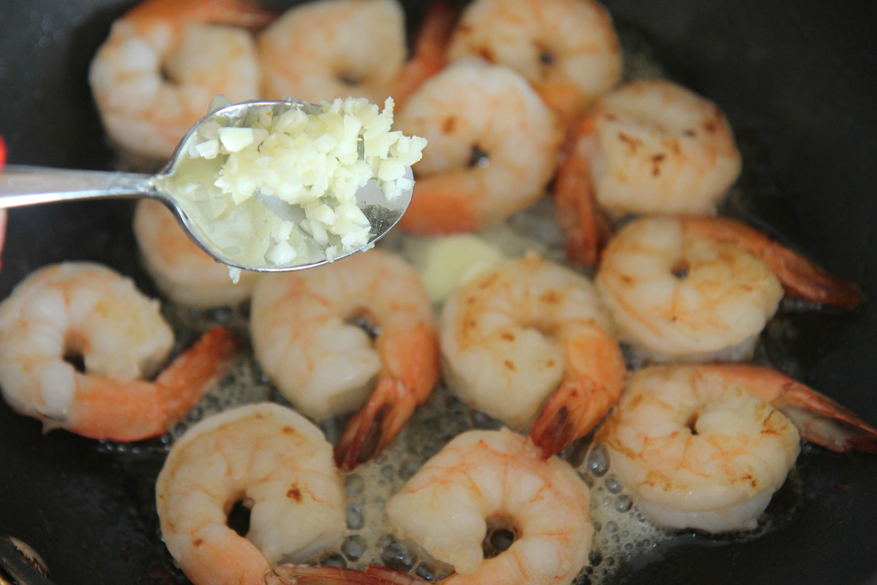 a spoon of fresh garlic and shrimp in a skillet.