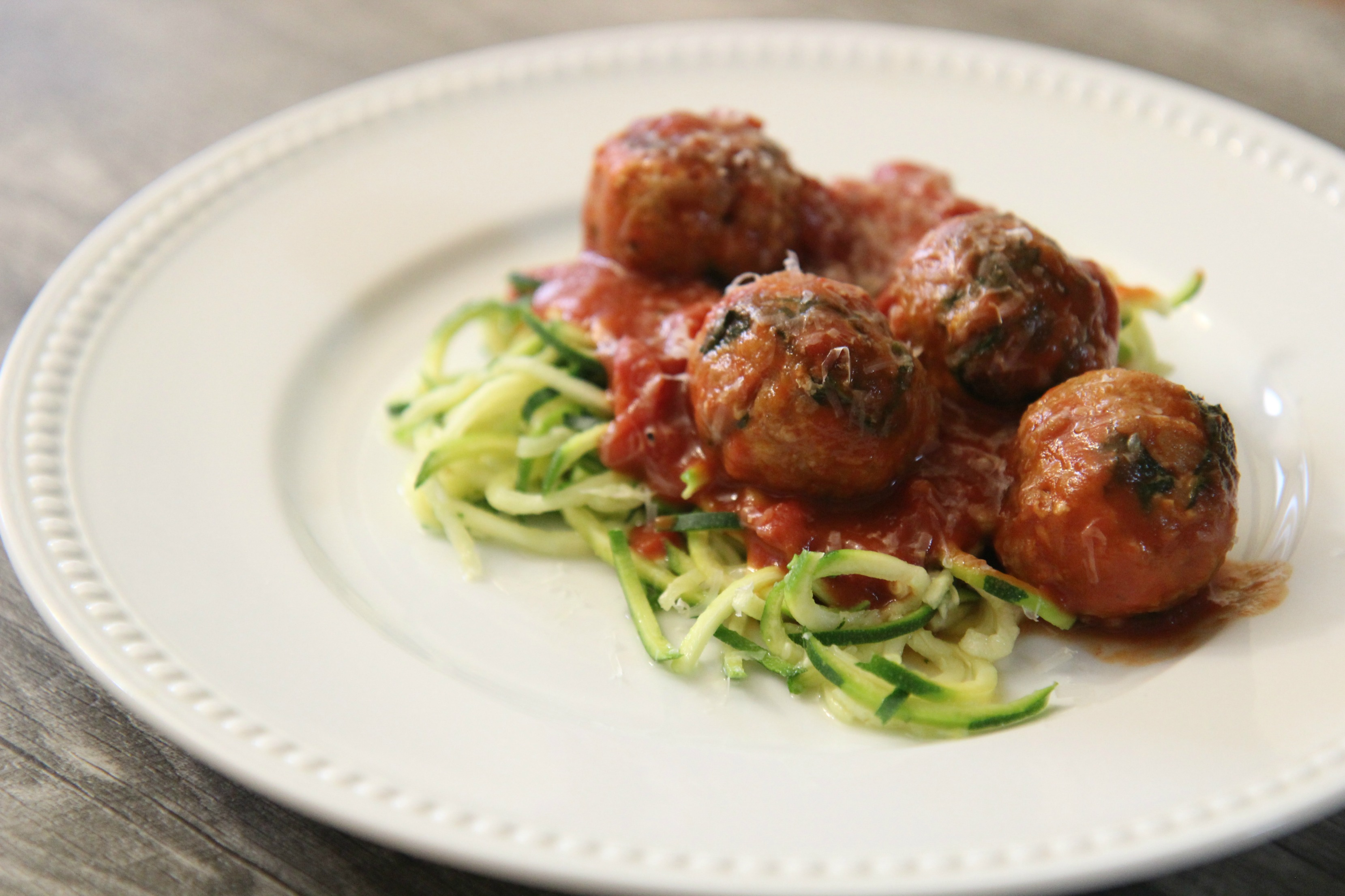 Baked turkey meatballs with spinach in tomato sauce and served with zucchini noodles
