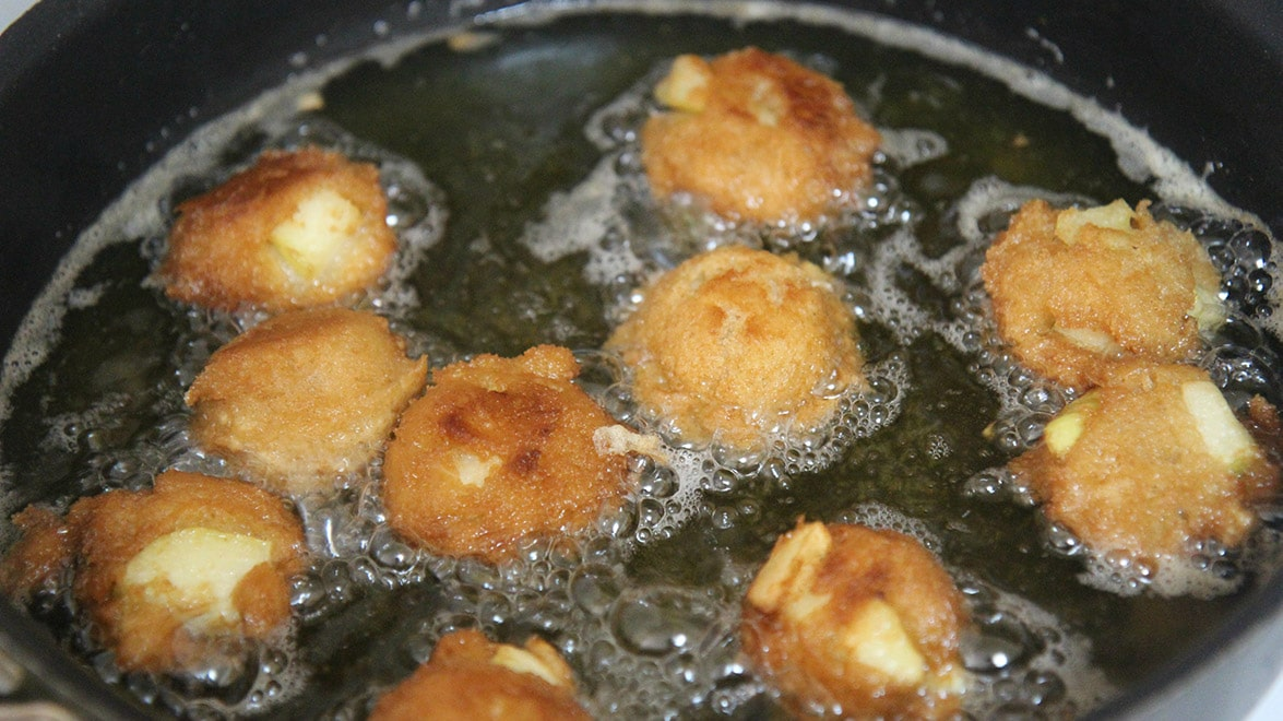 ten apple fritters frying in a skillet with hot oil.