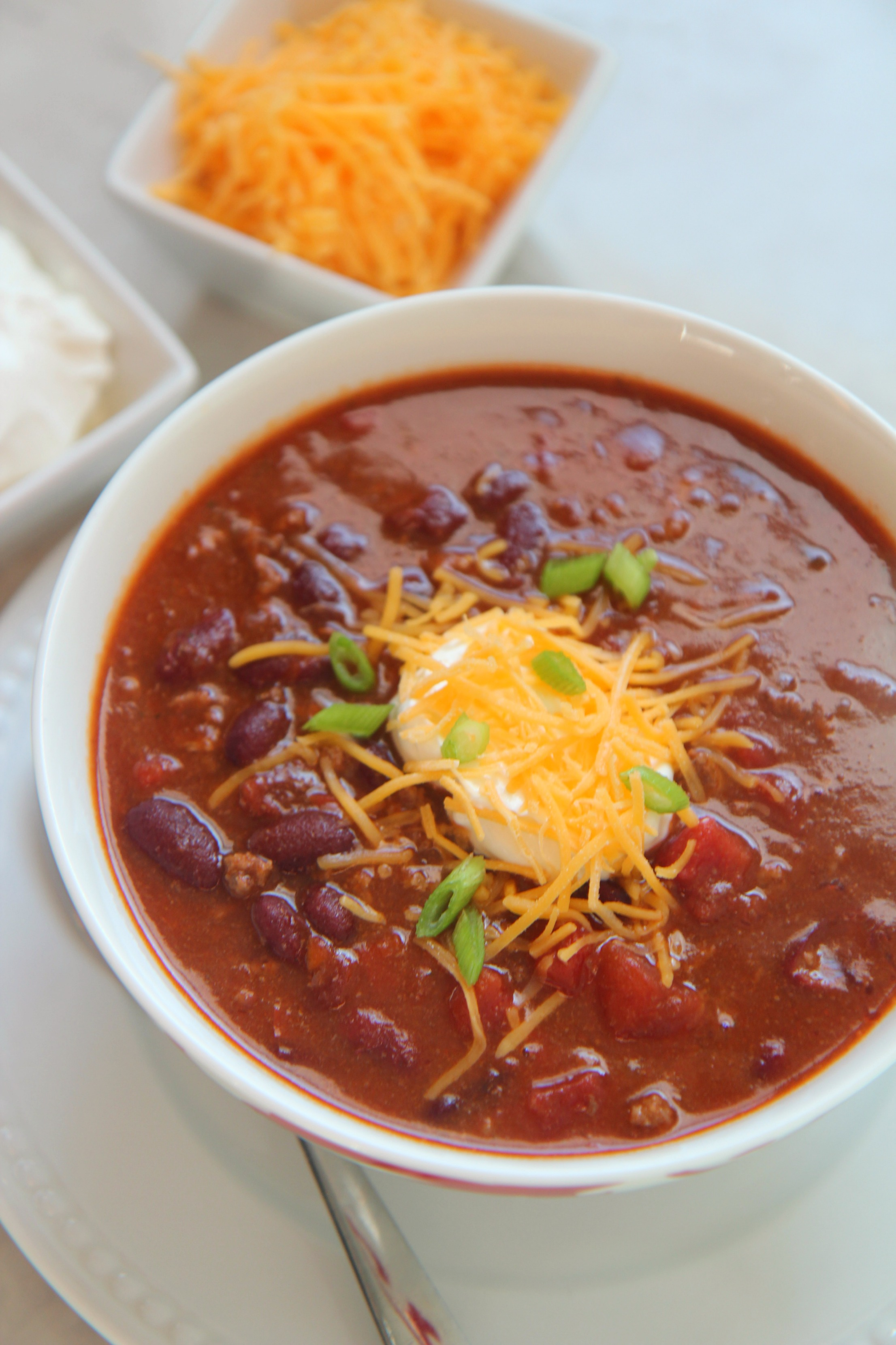 Chili with sour cream, cheddar cheese, and scallions in a white bowl with a spoon, cheese, and sour cream on the side.