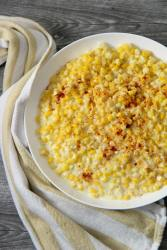 creamed corn in a white plate with a yellow and white kitchen towel on the side.