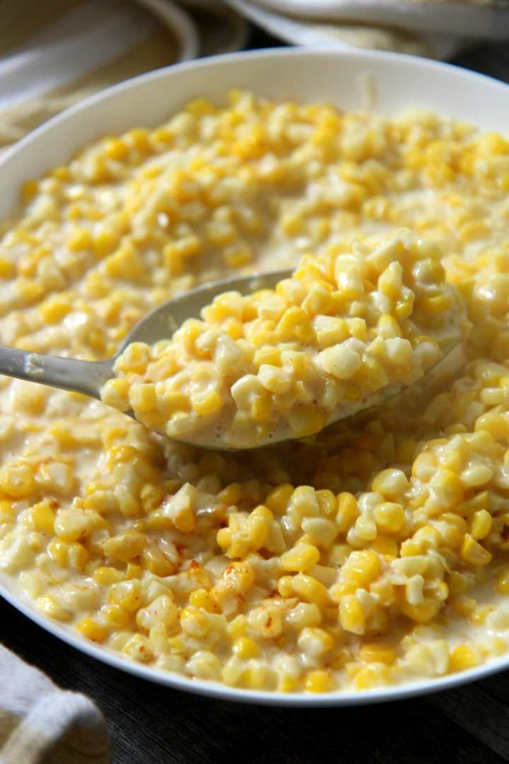 a spoon lifting creamed corn from a bowl.