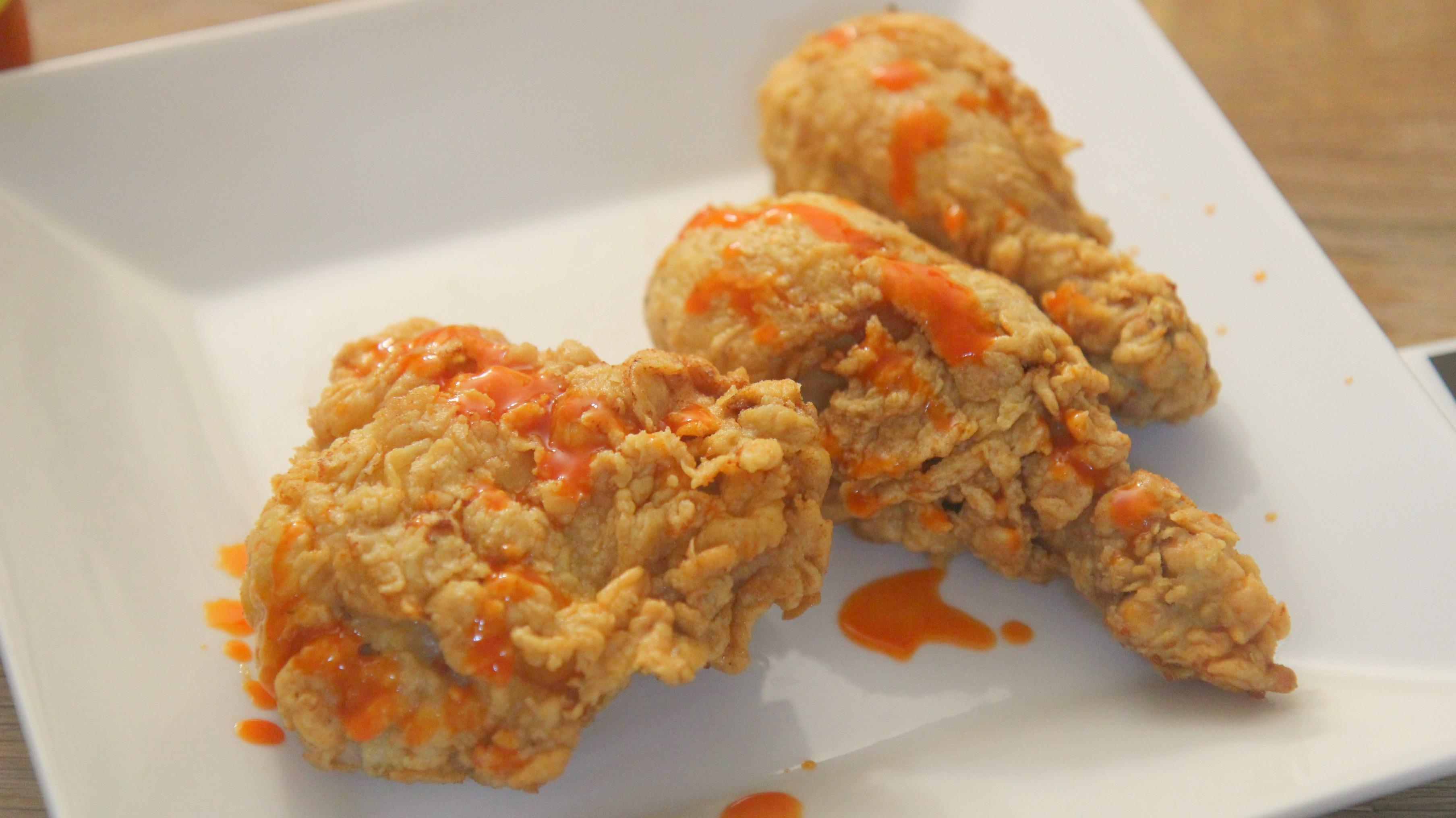 Crispy fried buttermilk chicken drizzled with hot sauce