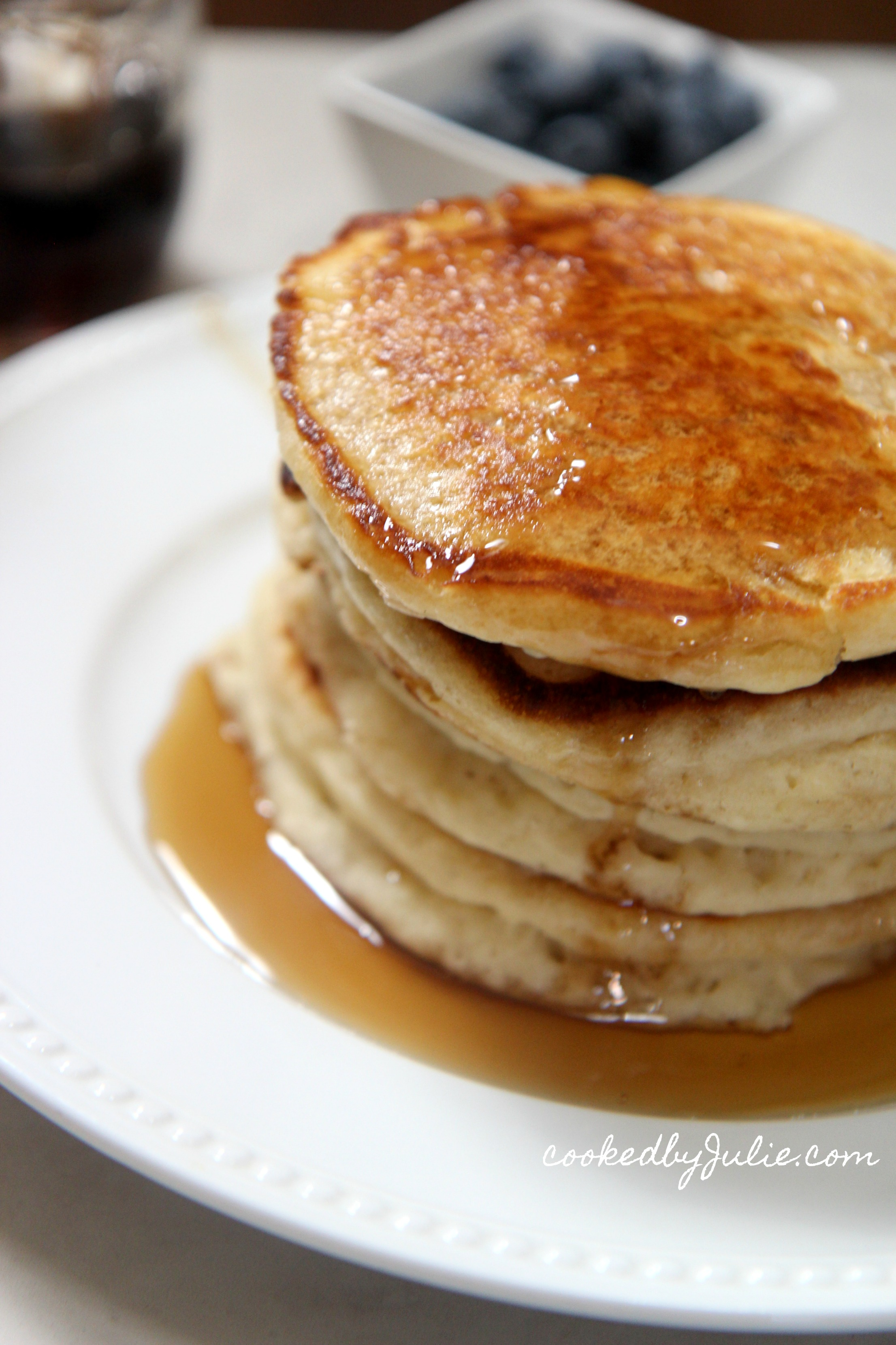 four pancakes on a white plate with maple syrup