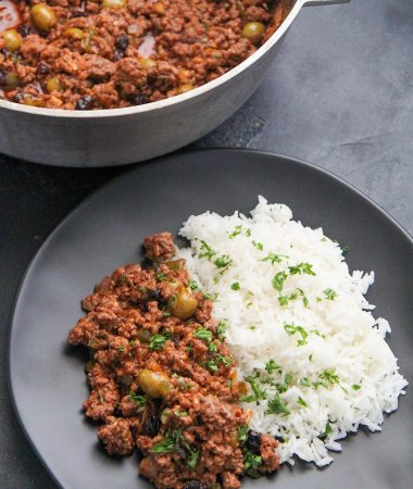 ground beef over white rice on top of a white plate