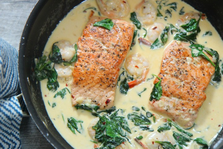 creamy salmon and shrimp in a pot with a blue towel on the side