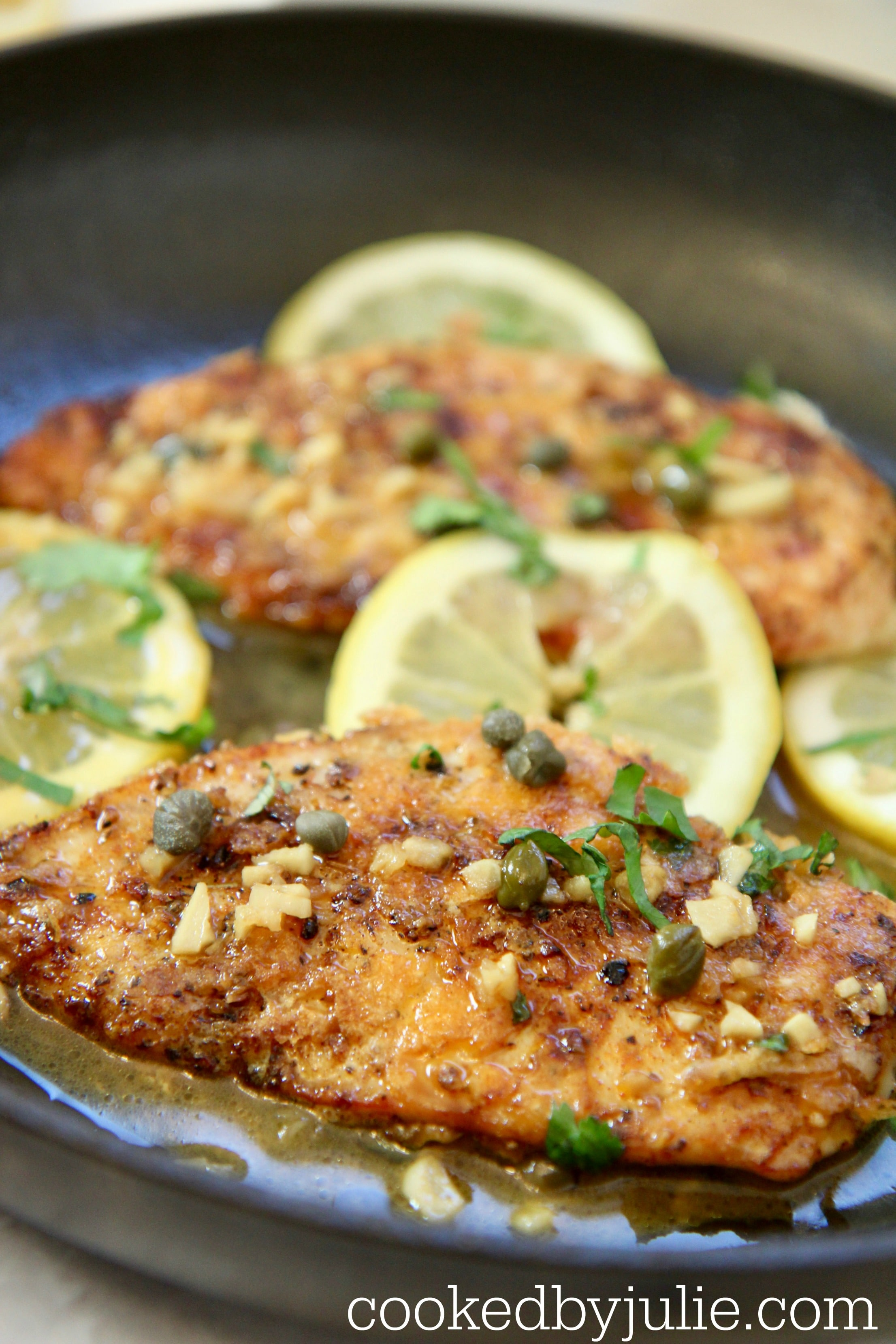 chicken in a skillet with sauce, capers, lemons, and parsley.