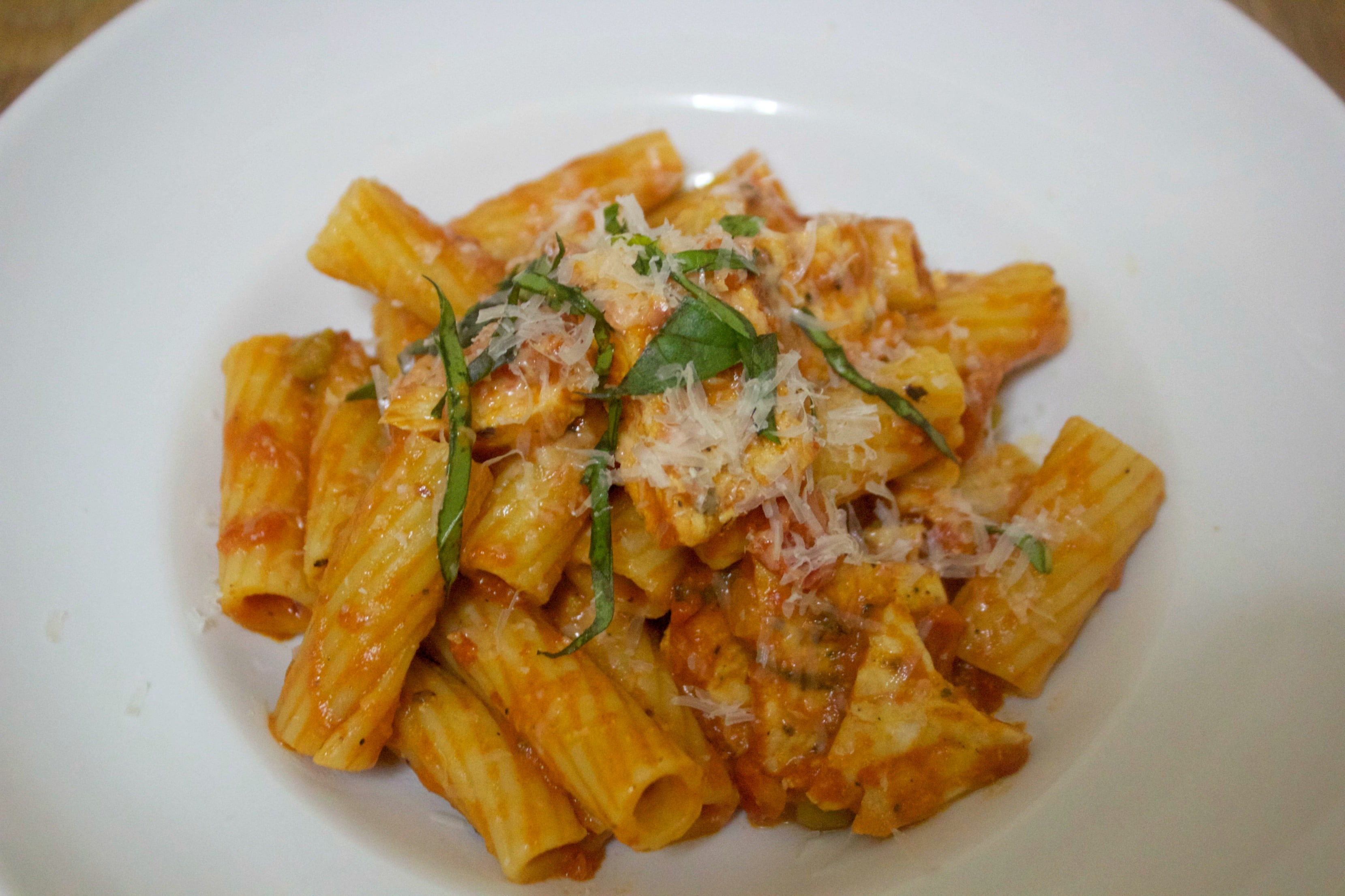 Spicy chicken, rigatoni, parmesan cheese, and fresh basil in a white bowl.