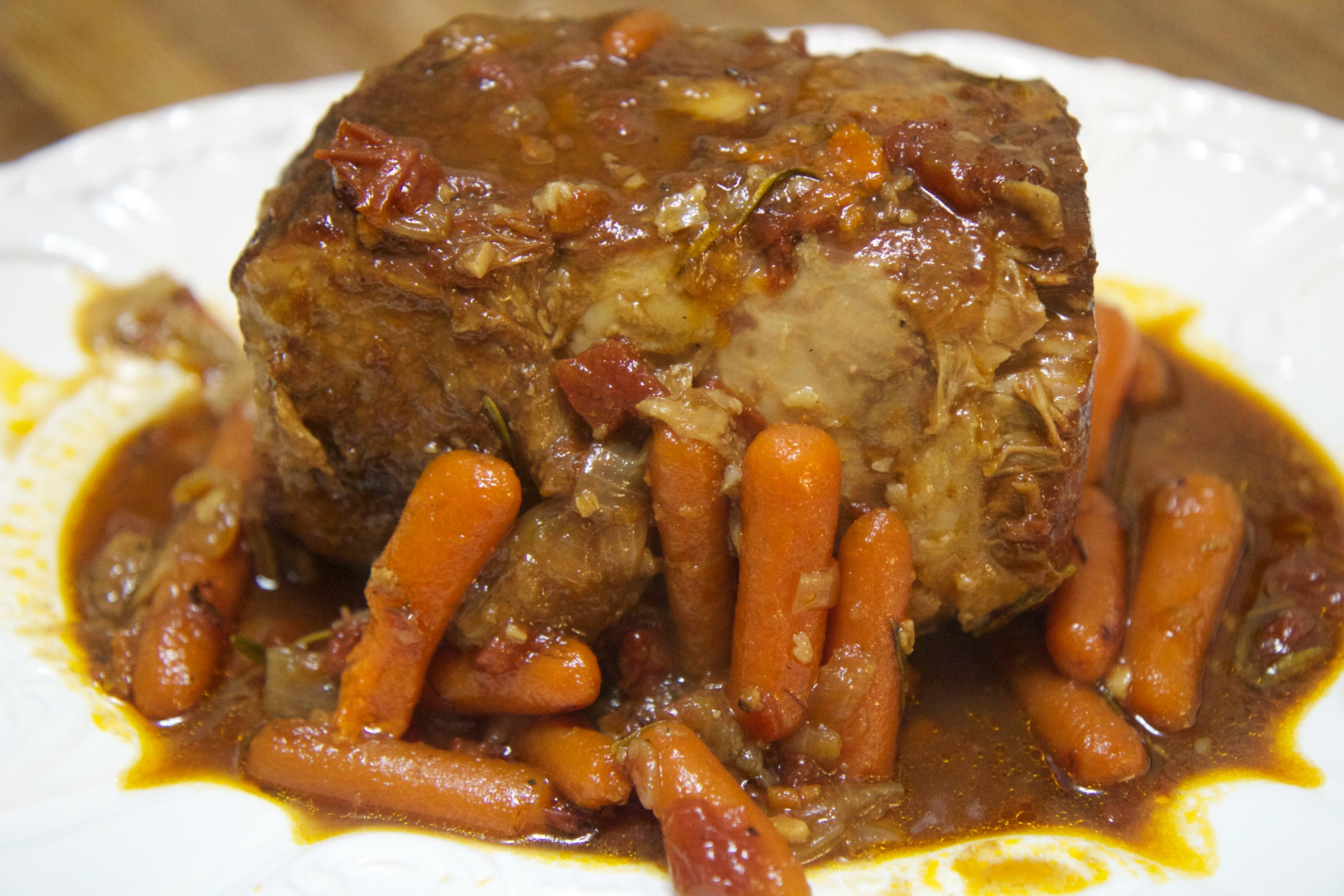 pot roast with vegetables on a white platter.