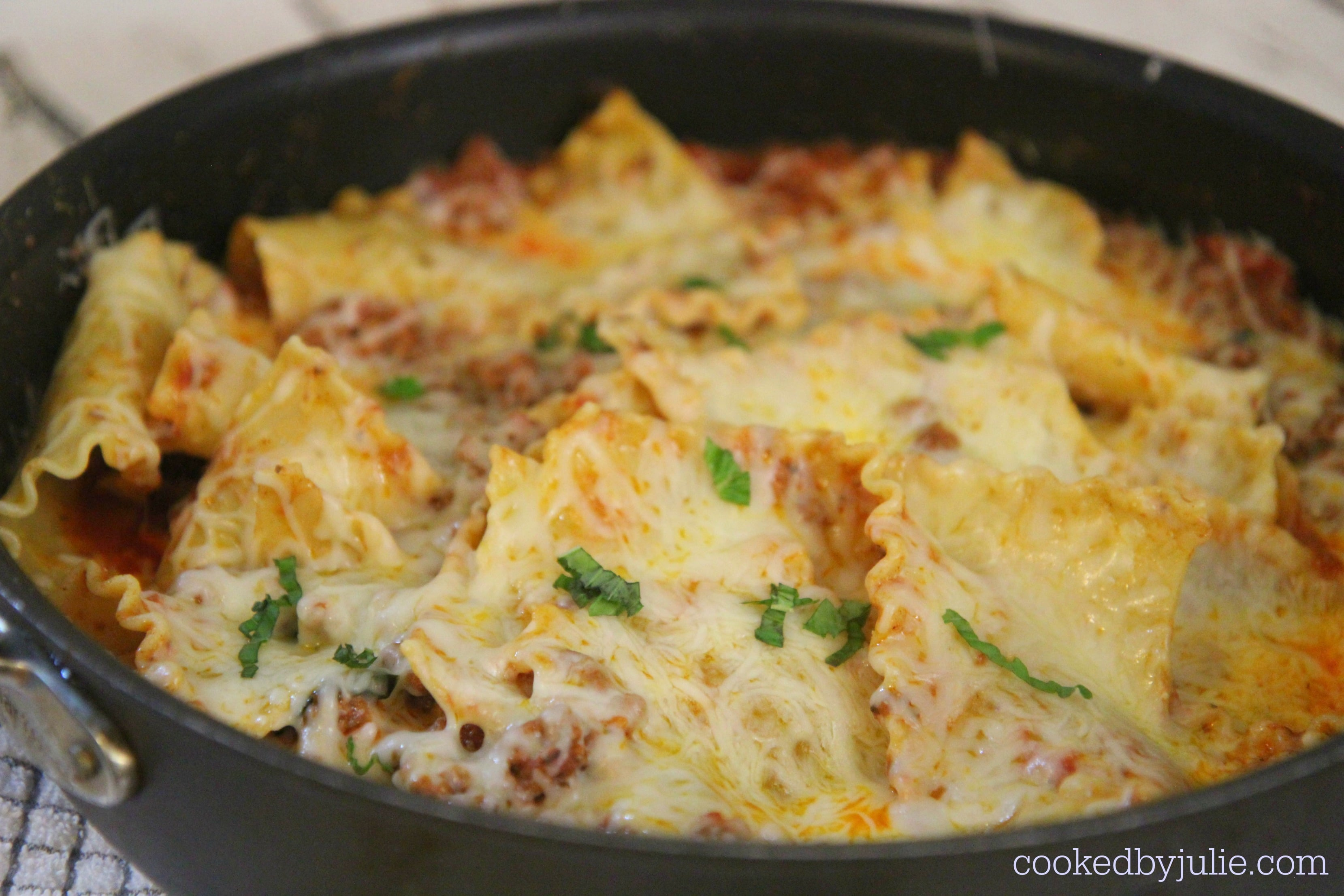 lasagna pasta, fresh basil, sauce, and cheese in a skillet.