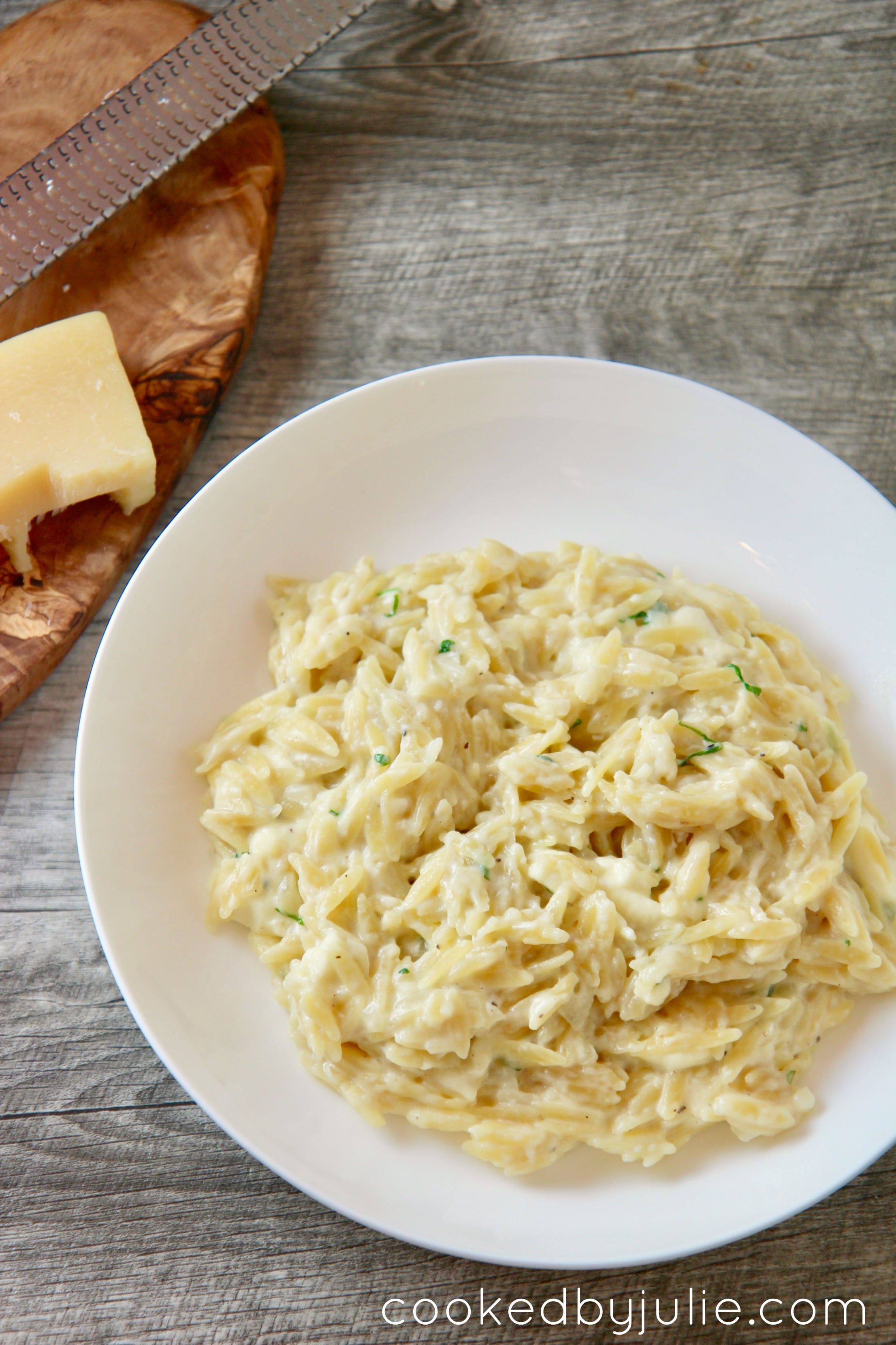 creamy garlic parmesan orzo sprinkled with parsley and served with freshly grated parmesan cheese