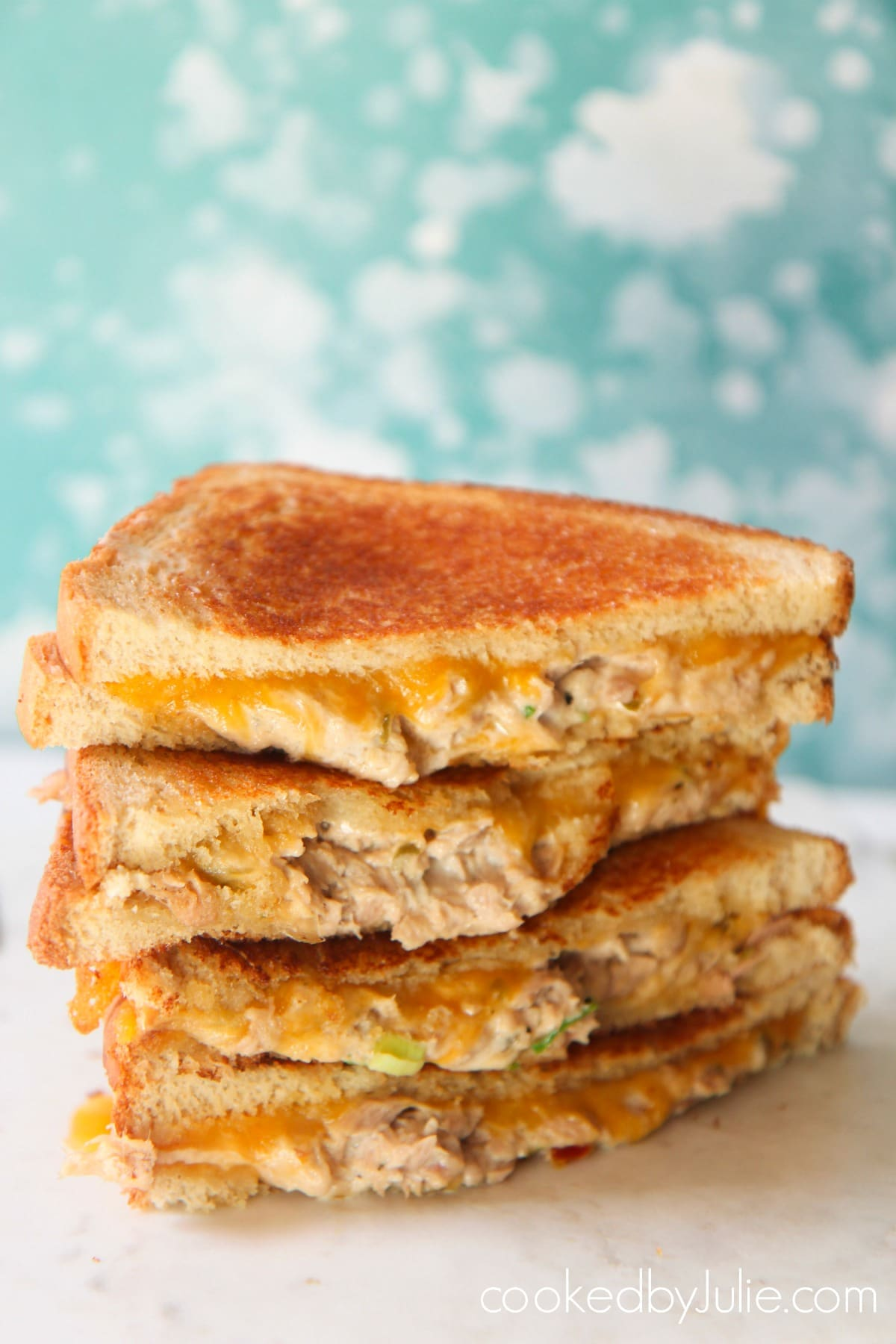 Four tuna melt sandwiches on a white surface with a baby blue and white backdrop.
