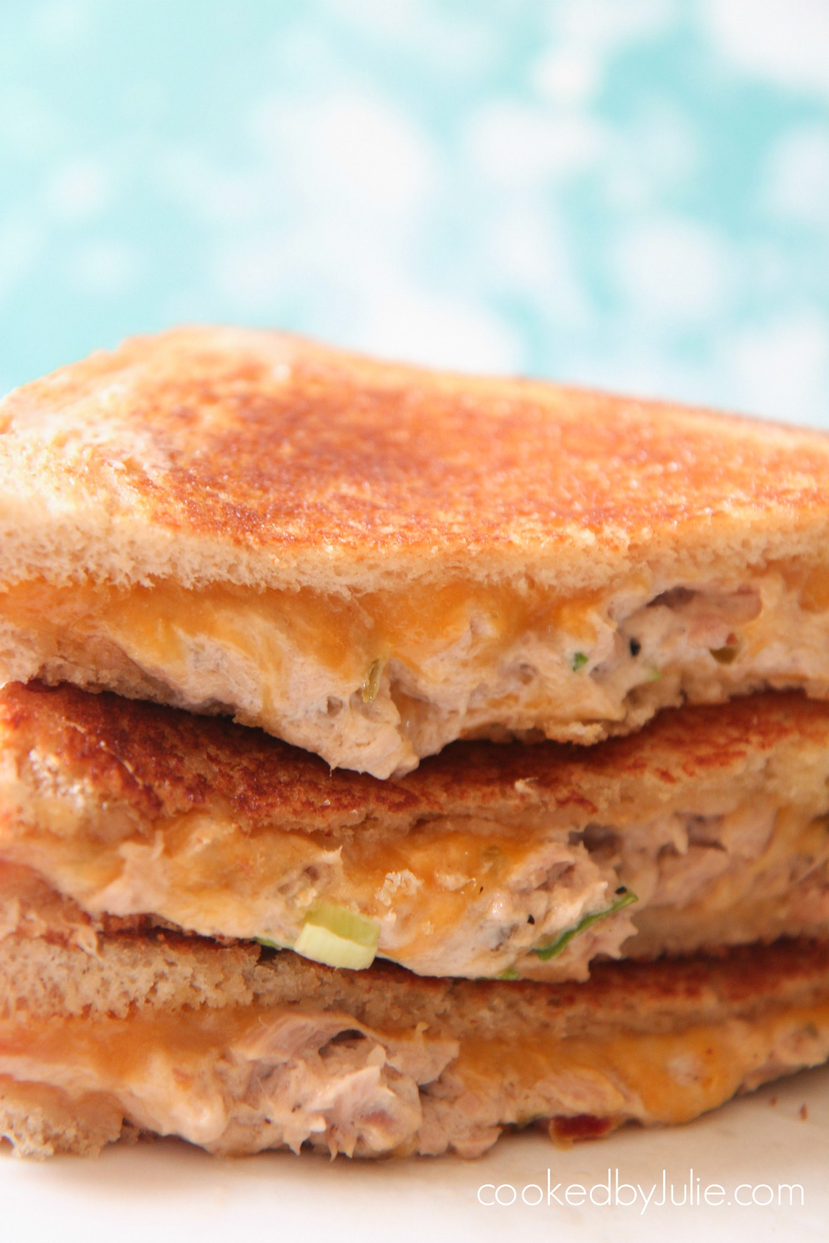 Three tuna melt sandwiches up close with a blue backdrop.