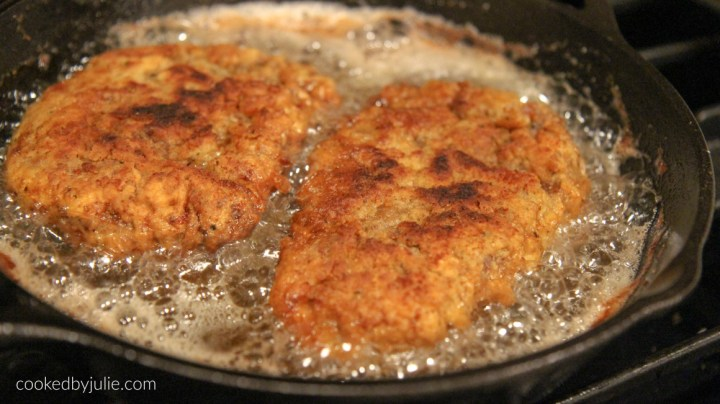 two chicken fried steak cutlets frying in an iron skillet with oil.