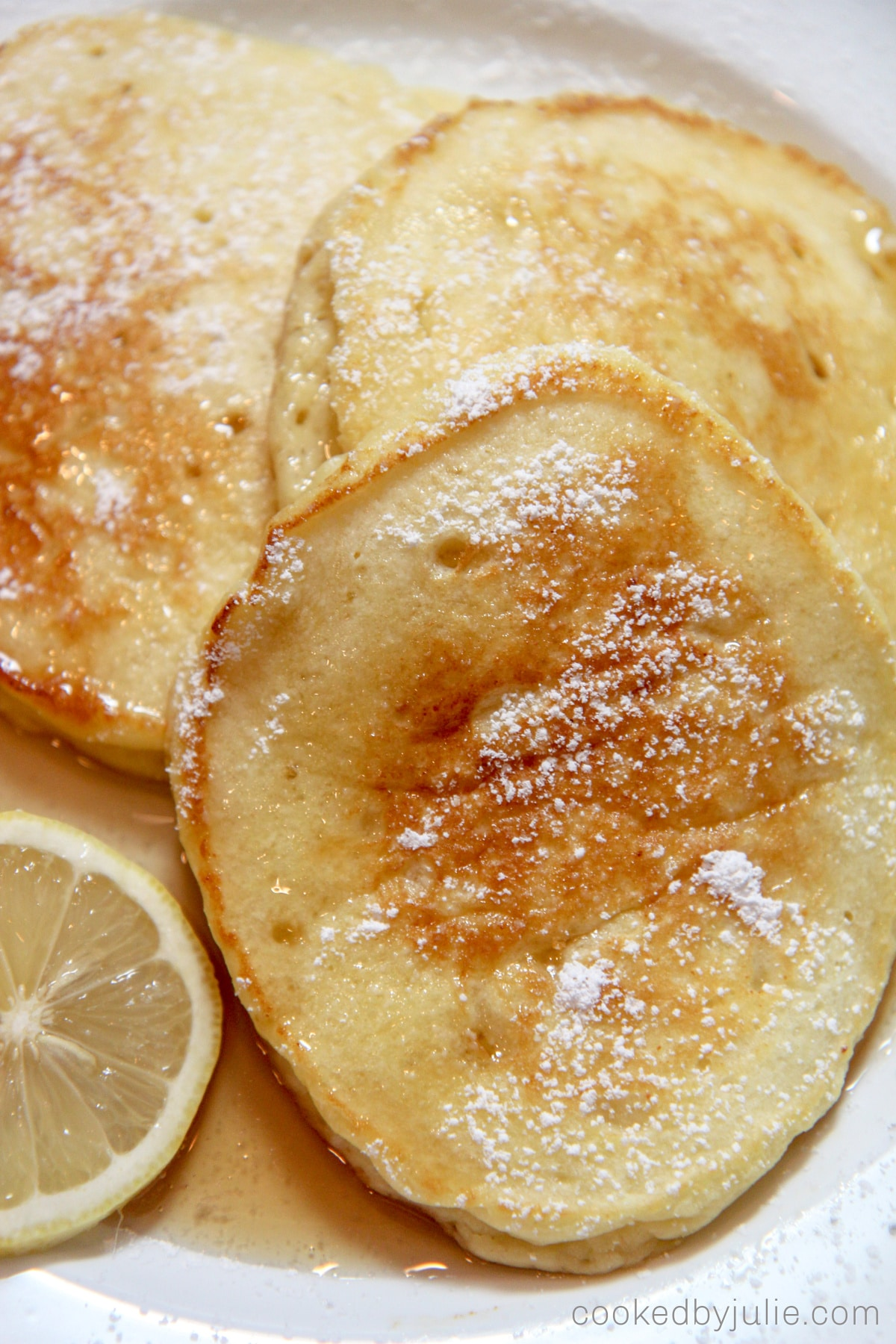 Three pancakes with powdered sugar, lemon slices, and syrup on a white plate up close.